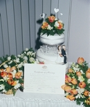 Wedding cake: Setting with bouquets & the certificate.